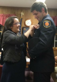 Captain Pat Hawkins having his badge pinned on by his significant other Susan Vecoli